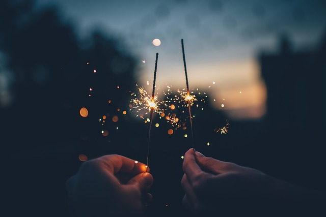 Hands holding sparklers in the dark